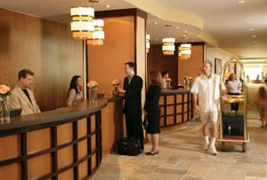 """A teak-accented reception area combined with warm tangerine hues and fresh flowers create an atmosphere of """"approachable luxury"""" during check-in."""