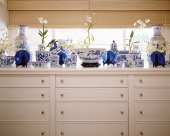 Antique blue glass plates and Chinese blue-and-white porcelain share a naturally lit spotlight on a custom hallway storage cabinet. Potted orchids and fresh flowers add height, depth, and life.
