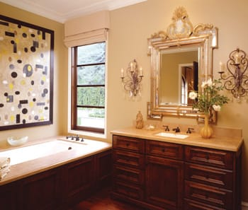 Walnut and limestone pair up in the master bath. A gilt mirror and crystal sconces provide contrast to the contemporary art.