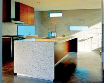 The island becomes a mega workspace and focal point of the open kitchen. Its top is custom-mixed poured terrazzo of natural rocks and glass by Modern Homes.