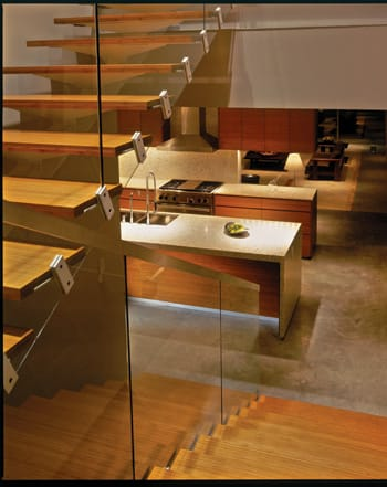 A modern bamboo staircase leads down to the kitchen, where Nichols designed the cabinets with integral pulls out of formaldehyde-free bamboo with cold-pressed laminate interiors.