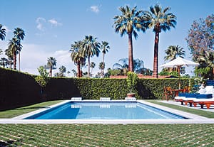 Manicured landscaping, a wooden café table and chairs, and comfortable, cushioned chaise lounges balance the water element of this Palm Springs pool. Ted Tuttle designed the home and grounds.