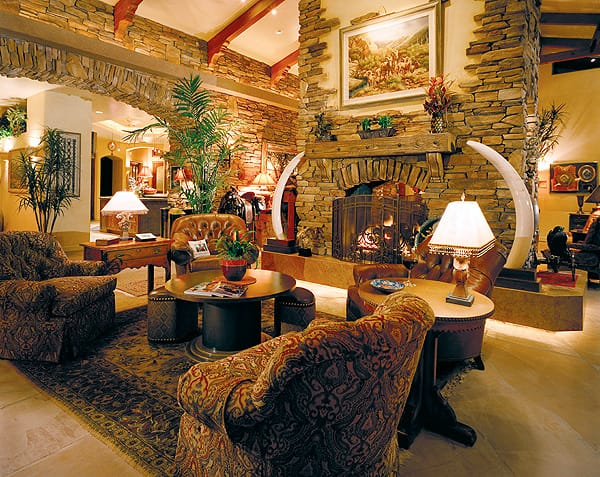 The great room sits at the center of the home and captures its spirit with stone, wood, and a magnificent double-sided fireplace.