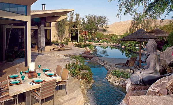 A waterfall next to a seated figure of Buddha in the foreground splashes down into a meandering stream at this home in Bighorn Golf Resort. Behind it, what looks like a pond is actually a Pebble Tec swimming pool, complete with a sandy beach-style entry at one end and a traditional entry at the other. Photo credit: Ethan Kaminsky.