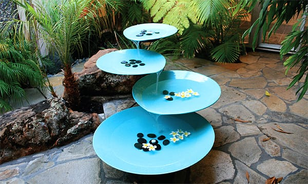 The sound of falling water soothes on this midcentury-style, four-tier fountain by Modern HQ. The descending metal tiers in azure are reminiscent of oversized lily pads. River rocks and floating flowers on each level add a finishing touch; $1,199. www.modernhq.com.