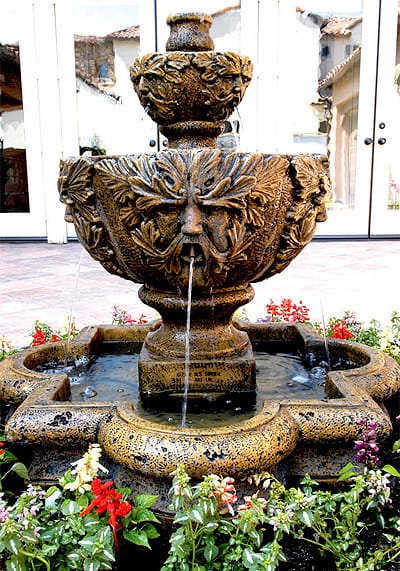 """A """"father nature"""" pattern repeats on both levels of this two-tier fountain that sits on a patio designed by Green Scene Landscape. Evaporation from the fountain helps cool the space around it. Photo credit: greenscenelandscape.com."""