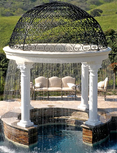 A waterfall gazebo by Green Scene Landscape is a fantastic example of a feature that incorporates sight, sound, and the cool sensation of water as it sprays down into a swimming pool. Photo credit: greenscenelandscape.com
