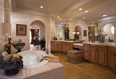 Arches and hand-painted tile mosaics carry the Old World theme into bathrooms.