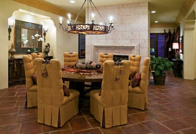 """Gold, red, and heavy wood furnishings complement dark stone and a """"candle"""" chandelier."""