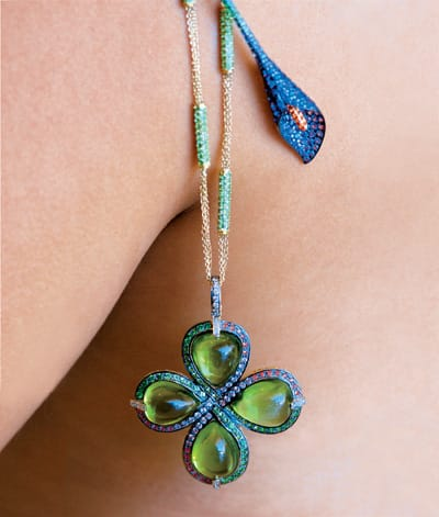 Clover pendant with 72.5 carats of peridot and multicolored gems. 18K yellow gold chain with tsavarites. Calla lily pin with amethysts, sapphires, and tsavarites. All from Leeds & Son Fine Jewelers
