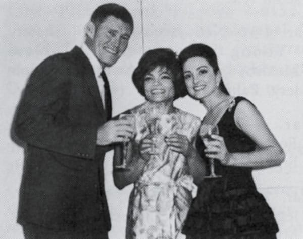 Actor Chuck Connors and his wife toast Eartha Kitt.