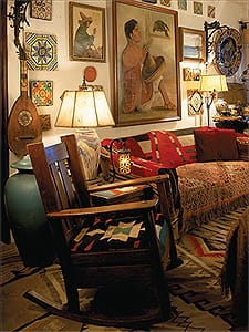 Spanish colonial antiques specialist Martin Newman has decorated his Palm Springs residence with the crème de la crème of his collections. In the living room, an arts and crafts oak rocker, circa 1910, has a cushion made from a Germantown Navajo tapestry, circa 1900. A 17th century Italian lute, 1920s California tiles, wrought-iron lamps, and a Navajo blanket jostle for space with paintings, rugs, urns, and Mexican serapes reminiscent of the ones used by Newman for Bob Dylan's 1960s on-stage garb.