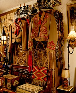 Newman's collection of early California fiesta and rodeo attire includes two embroidered and appliquéd wool gabardine jackets, hanging on an 18th century Spanish colonial polychrome pine armario. Newman displays the scarves, boots, shirts, and skirts worn by women, as well as the elaborate silver and leather trappings worn by their thoroughbreds. The wrought-iron lamp is 1930s Monterey.