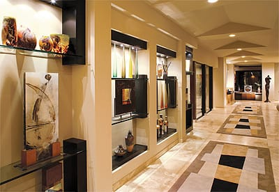 Recessed shelves in the main entryway create a safe place to display delicate glass and works of art. The wide hallway is welcoming and the bold patterns on the rugs appeal to adults and children alike. The durable density and neutral colors can handle high traffic and prevents slips and falls.