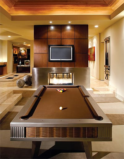 The sunken billiard room. A doublesided fireplace joins it with the dining room.