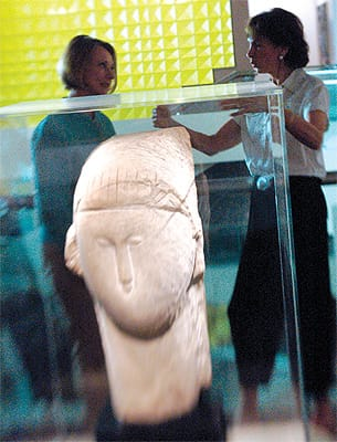 """While Henry Moore's sculptures represent the strength of the Weiner collection, this stone sculpture, """"Head"""" (1910-11) by Amadeo Modigliani is the exhibition's pièce de résistance. In the background, Curator Katherine Hough (left) and Gwendolyn Weiner discuss the piece, which had been exhibited on the third floor."""