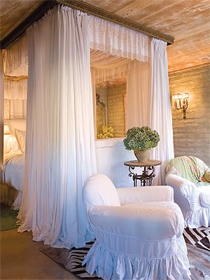 Suzanne Somers made the most of her linen collection in the master bedroom, creating a dreamy canopy on a bed from India. The flagstone floor, adobe walls, and wood ceiling temper the feminine touch.
