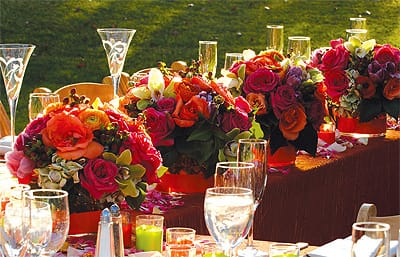 Vases on the bridal party's table hold bridesmaid bouquets post-ceremony to save on costs of additional centerpieces.