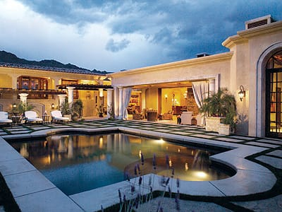 The courtyard of this Tuscan-style residence with interior design by William Miller Design sets a luxurious ambiance of indoor/outdoor living in Palm Desert.