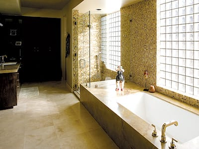 Travertine flooring, Wenge wood cabinetry, tumbled and flamed marble, and mosaic accents distinguish the master bath.