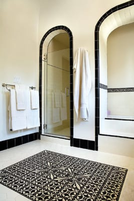 Not So Basic Black -  A modern take on a classic 1940s style offers subtle glamour in this bathroom by Mission Tile West. A border of liner tiles around the tub complements the hand-painted Malibu tile in the room's center, while solid black tiles around the arched entries to the shower and tub offer just enough contrast to the clean white walls; call for pricing. Mission Tile West, 75100 Merle Drive, Suite 3, Palm Desert, 346-2602.