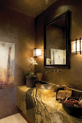 GOLDEN GLOW - Bill iller designed this powder room around the Juperana granite vanity and amber glass sink. The walls were hand-faux-finished by Las Palmas Painting of Palm Springs in copper metallic tones. 836-9199, www.williammillerdesign.com.