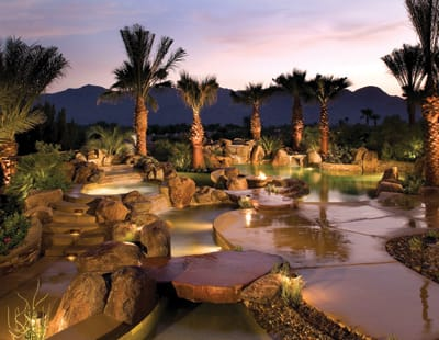 One hundred tons of boulders were hauled in to build this show-stopping pool in The Estancias at Rancho La Quinta. Coachella-based Teserra won an Association of Pool and Spa Professionals gold award for this dramatic poolscape (the fourth it created for the homeowners) that incorporates three water features, a grotto, stream, bridge, and fire pit with a swim-up/walk-down option. More than 20 dimmable lights shine on the bends of the stream, fountains, and stacked-stone water features, while several pumps control their speed and flow.