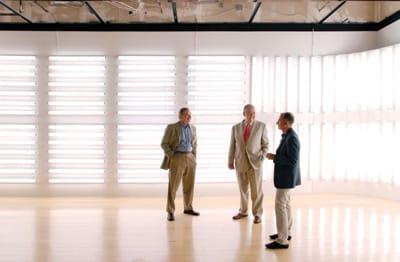 Museum Director Steven Nash (left), Board Chairman Harold Meyerman (center), and Deputy Director for Art Daniell Cornell walk through the museum's newly relocated Kaplan/Ostergaard Glass Center.