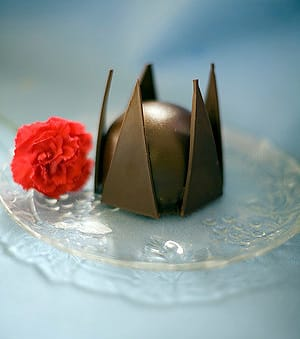 A favorite French delicacy, The Bomb is a dark chocolate ganache dome filled with chocolate mousse with raspberries in the center. Pastry chef C. William Austriut of La Quinta Baking Co. created the example pictured.