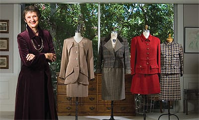 Claire Shaeffer, wearing a maroon velvet coat inspired by Yves Saint Laurent (a pattern she created for Vogue), has collected many significant fashions, including (from left) a YSL suit exhibited at the Metropolitan Museum of Art, the YSL taupe faille Nan Kempner collectible, a late-'70s cherry bouclé Chanel ensemble, and a novelty wool Chanel suit with removable cuffs.