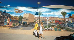 Indio is home to seven hand painted murals in the downtown. A couple walks by the Transportation Mural on the side of Clark's Truck Stop.