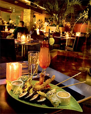 An exciting choice at The Tropicale is The Pupu Platter, an exotic combination of Coconut Tiger Shrimp, Thai Chicken Satay, Korean Beef Skewers, Vietnamese Spring Rolls, and Crispy Pot Stickers, shown with a Papaya Cooler on the romantic patio.
