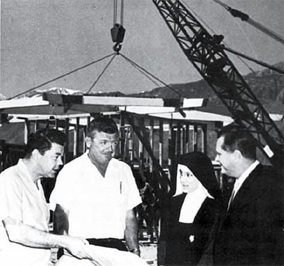 Project inspector Dick Wilson, foreman John Woodleif, Sister Jeannette, and architect William F. Cody discuss construction as the chapel roof is raised into place.
