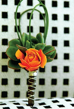 Weddings at funky boutique hotels often inspire bold floral colors, like this orange rose boutonniere (Artisan).