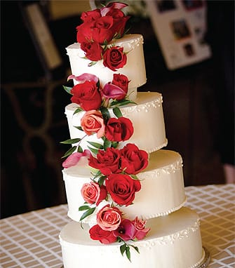 """Red Roses, Red Roses!"" is the theme of this terrific tower by Exquisite Desserts. While smooth fondant cakes are best for appliqué work, the bakery says traditional Italian meringue buttercream cakes like this one are a hit for their rich flavor. Real butter and Tahitian vanilla combine to create an irresistibly creamy confection that brings guests back for a second piece!"