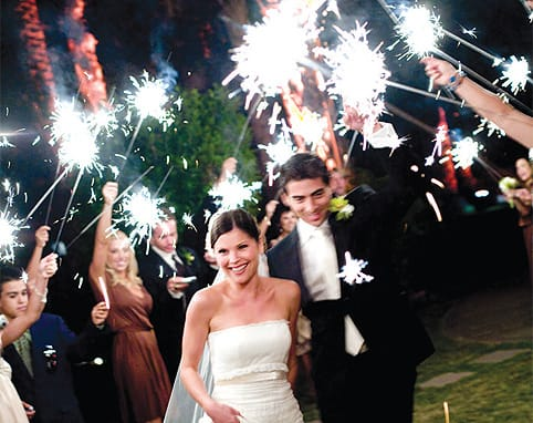 "Peter and Callie Karvelis enjoyed a dramatic husband-and-wife welcome at their Cree Estate reception thanks to Callie's mother, Debbie, who found 20-inch sparklers. The long wands lit the way from the couple's starry entry through their first dance, after which they invited everyone onto the dance floor. ""Debbie chose sparklers to add a unique touch to our entrance and to set a festive, upbeat tempo,"" Peter says. ""We wanted everyone energized and ready to dance with us."""
