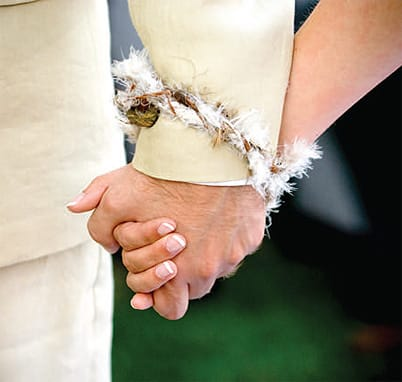 Incorporating a Native American tradition, the couple had their wrists tied together with a delicate string of feathers.