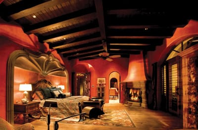 Exposed wood beamed ceilings, thick Venetian plaster, ceiling fans, a stone-trimmed fireplace, and rich furnishings ensure overnight visitors recline in comfort in this romantic guest casita.