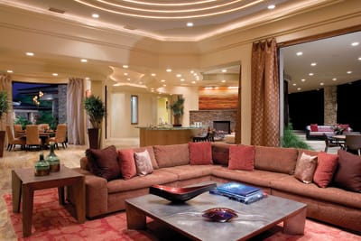 With walls in a creamy neutral, this curvaceous contemporary shows off through its furnishings, all in a warm color palette of bright bittersweet, saffron, and cinnamon. The family room's plush, L-shaped sofa faces a granite fireplace, while the room's backdrop becomes the artwork above the living room fireplace, a Murano glass globe chandelier over the formal dining table, and the spacious outdoor living room. The blue perimeter lights in the stepped ceiling over the sofa set a softer mood at night. A two-toned, coral-colored Tibetan wool rug, handmade with an environmentally green process in Nepal, completes the look.