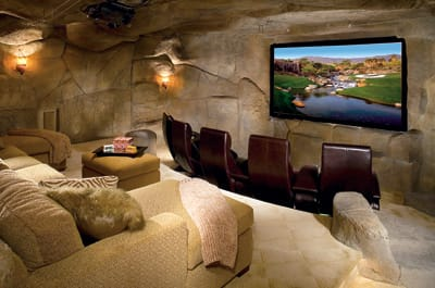 An Obol projector, 119-inch, high-definition onyx projection screen, in-wall speakers, and plush custom seating for 10 provide movie-star treatment to family and friends in this boulder-walled theater on the lower level. The faux effect complements the natural rock walls of the outdoor grotto.