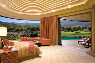 "When floor-to-ceiling glass pocket sliders disappear into the walls of this dramatic master bedroom, the sunrise over the Santa Rosas and an unobscured view of the 11th fairway of Bighorn Golf Club's Tom Fazio-designed Canyons Course welcome the outdoors in. The flip of a switch closes doors and draperies that are secured and operated by brushed-nickel hardware from Germany. Rope lights tucked inside the sculpted folds of the ceiling set the mood for dreaming or stretching out on the semicircular sofa that hugs the curves of the room. ""The carpet in here feels as soft as cotton balls on the bottoms of your feet,"" says interior designer Rhonda Parks."