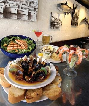 Just a few items from the extensive menu of fresh fish and seafood, clockwise from the bottom — Canadian Black and New Zealand Green Mussels in a Chardonnay tomato basil sauce; Grilled Salmon Caesar Salad; Grilled Halibut served with rice and coleslaw; and shrimp cocktail. Libations are a Shanghai Reds Martini and Bahia Beer from El Salvador.