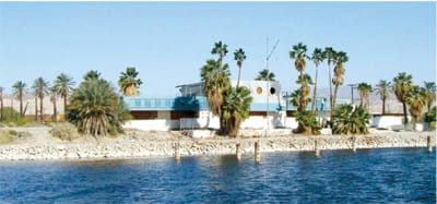 View of the Yacht Club property today from southwest across the water, framed amid untrimmed palm trees