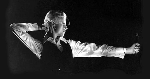 "This photograph shows David onstage during the Station to Station tour as his character ""The Thin White Duke"" assuming a pose he calls ""The Archer."" The pose ended a song and when his fingers released the imaginary arrow from the bow it was the cue for the lighting director to fade to black. David tells me this is one of his favorite photographs of his onstage characters. I am most flattered to have been the photographer who captured it. – John Rowlands, as excerpted from his book Rock & Rowlands Flashback."