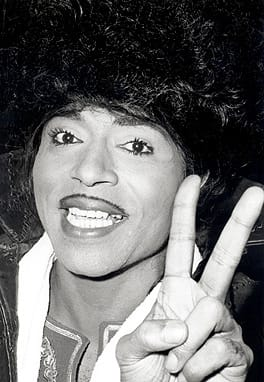 "It's easy to say that working with Little Richard was always a scream. He was flamboyant and charged every night I spent on the road with his tours. As his photographer I could go anywhere onstage as long as I did not block his line of sight with the audience. … One night he did a Jerry Lee Lewis prank and poured lighter fluid on the ivory keys of a full grand piano and lit them on fire. The stage manager passed out but ""The beauty was always on duty"" as Richard knew lighter fluid burns clean and no real damage was done. – John Rowlands, as excerpted from his book Rock & Rowlands Flashback."