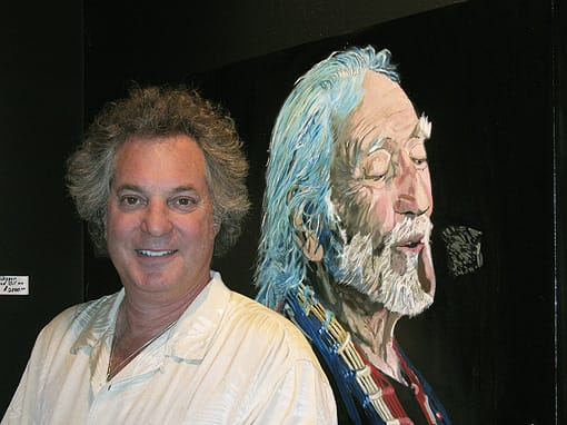 Max von Wening stands in front of his portrait of Willie Nelson, signed by Willie Nelson.