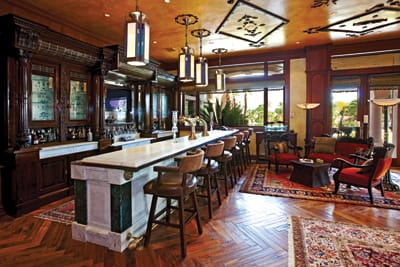 Chevron-patterned wood flooring, ornately carved cabinetry, a polished Carrera marble bar with brass beer taps and foot rail, and art deco light fixtures create a luxurious ambiance for entertaining guests.