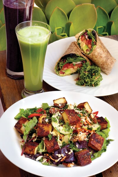 Organic Veggie Wrap: hummus, mixed greens, avocado, jack cheese, pumpkin seeds, and balsamic dressing wrapped in a sprouted multigrain tortilla. (Bottom) Asian Tofu Salad: flavored tofu, cabbage, carrot, cucumber, brown rice, and roasted almonds on mixed greens with peanut and sesame-ginger dressing. Shown with Acai Energy Smoothie: acai, triple berry (blueberries, raspberries, and strawberries), banana, and orange — and Green Drink made with kale, celery, cucumber, green apple, lemon, and ginger.