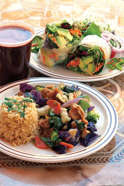 """Raw Garden Wrap: hummus, organic mixed greens, shredded carrot, red onion, tomato, alfalfa sprouts, avocado, and seasonal raw vegetables wrapped in rice paper. (Bottom) Garlic Ginger """"Chicken"""" Stir Fry: seasonal vegetables and soy """"chicken"""" in garlic-ginger sauce, served with organic brown rice. Shown with hibiscus iced tea."""
