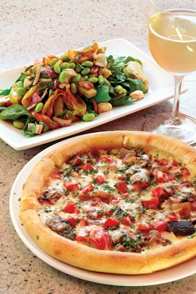 Roasted Vegetable Salad: spinach, mozzarella pearls, yellow tomato, edamame, artichoke, red pepper, onion, basil, lemon, balsamic vinegar, and olive oil. (Bottom) Vegetarian Pizza: grilled eggplant, onion, zucchini, bell peppers, tomatoes, fontina, and roasted garlic sauce on wood-fired crust. Shown  with Greystone Cellars chardonnay.